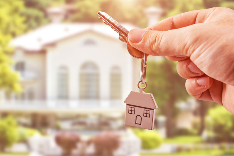 Buying a New Home? Remember to Consider These 4 Insurance Factors person holding keys to a new home